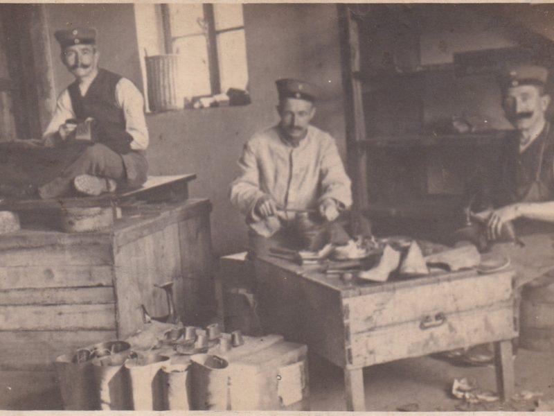 Zu sehen ist Karl-Martin Wins (1. von links) in einer Werkstatt bei der Schneiderarbeit zusammen mit zwei Schustern, einer davon ist sein Bruder.