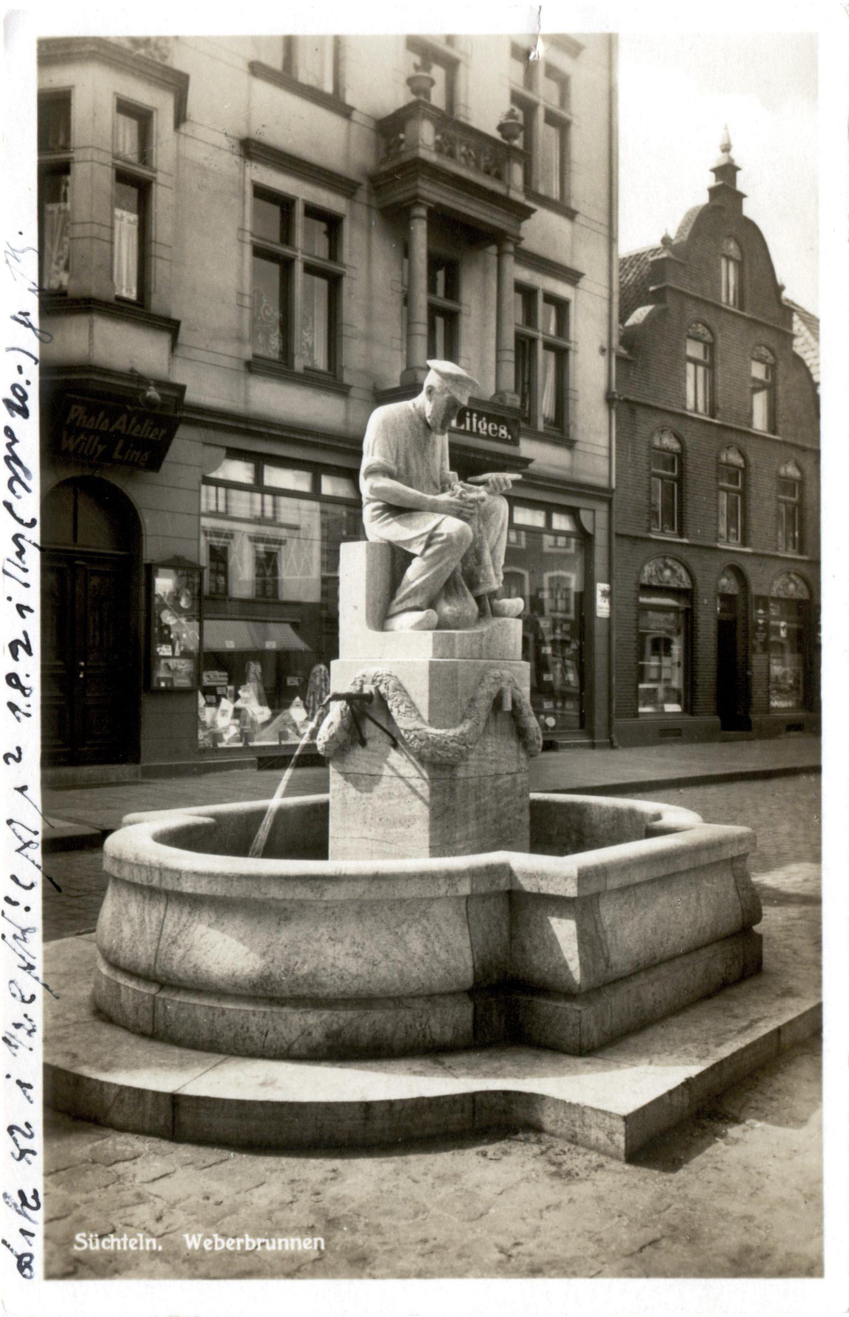 """Weberbrunnen in Süchteln um 1921. Im Hintergrund befand sich das Ladenlokal der Familie Lifges. In dem Gebäude findet man heute ein Geschäft der Kette """"ernstings family"""".; Quelle: Kreisarchiv"""